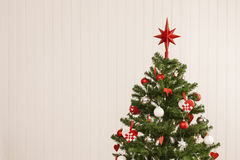 Christmas tree against a wooden wall Royalty Free Stock Photo