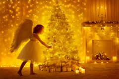 Christmas Tree and Angel Child with Candle, Girl and Presents. Christmas Tree and Angel Child with Candle, Girl Decorating Presents in Holiday Room with stock photos