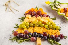 Christmas tree of appetizers: cheese, grapes, crackers. Christmas food concept, white background.