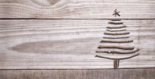 Christmas tree arranged from sticks on wooden sparkly grey backg Stock Image
