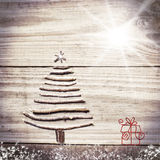 Christmas tree arranged from sticks on wooden sparkly grey background. Stock Photos