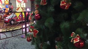 Christmas tree on the background of the carousel. Christmas tree on the background of the merry-go-round, red ornaments, toys, bows and balloons on the stock video