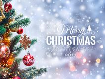 Christmas tree background and Christmas decorations with blurred, sparking, glowing and text Merry Christmas and Happy New Year. Royalty Free Stock Images