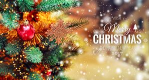 Christmas tree background and Christmas decorations with blurred, sparking, glowing and text Merry Christmas and Happy New Year. Stock Images