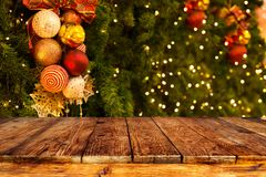 Christmas tree background with decoration and blurred light bokeh with empty dark wooden deck table for product montage.
