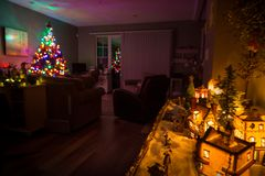 Christmas tree in the background and a model christmas village in the foreground. royalty free stock photos