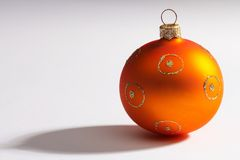 Christmas tree ball. Orange christmas glass ball with shadow on white paper, there is space for text left Stock Image