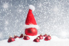 Christmas tree ball with santa hat in the snow Stock Photography