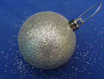 Christmas tree ball silver single , blue background royalty free stock photography
