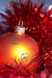 Christmas tree ball with tinsel. Orange christmas tree ball with red tinsel, closeup royalty free stock image