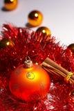 Christmas tree ball - weihnachtskugel. Orange christmas tree ball with cinnamon and red tinsel - orange Weihnachtskugel mit Zimtstangen und roter Lametta royalty free stock photo