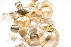 Christmas tree balls. Golden christmas tree balls with a ribbon on white Royalty Free Stock Images