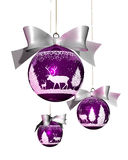 Christmas tree balls. One big and two small Christmas tree balls in violet with reindeer ornaments and a white ribbon Royalty Free Stock Photos