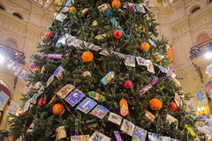Christmas tree with balls, candy and old postcards. Moscow, Russia - December 11, 2015: Christmas tree decorated with Christmas balls, candy and garland of old Stock Photos