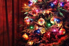 Christmas tree with balls, glowing garland and tinsel