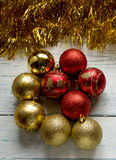 Christmas tree balls and golden shiny garland. Vertical frame. Christmas tree balls and golden shiny garland on a white wooden background. New Year. Vertical Stock Photos