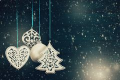 Christmas tree balls hanging against a wooden background. Christmas tree ornaments and balls hanging against a blue wooden background with snow and lights bokeh royalty free stock photography