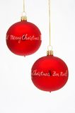 Christmas Tree Balls - Weihnachtskugeln. Two red Christmas Tree Balls with golden merry Christmas written on it on white background - zwei rote Weihnachtskugeln Stock Photography