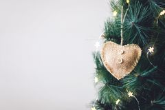 Christmas tree banner, background. Decorated Christmas fir tree with rustic burlap heart ornament and star light garland. Christmas tree banner, mockup royalty free stock photos