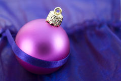 Christmas Tree Bauble. Christmas tree ball arranged with decorative purple fabric background Stock Photography