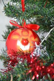 Christmas tree bauble. Detail of a Christmas tree decorated cheerfully with a red bauble rappresenting Rudolph the ed Nose Raindeer Royalty Free Stock Photos