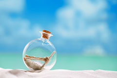 Christmas tree bauble in  message bottle shape  on beach. With seascape background Royalty Free Stock Photography