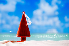 Christmas tree bauble in  red glass shape  on beach. With seascape background Royalty Free Stock Photo