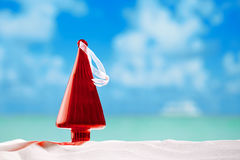 Christmas tree bauble in  red glass shape  on beach. With seascape background Royalty Free Stock Images