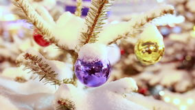 Christmas tree bauble under snow closeup. Shiny christmas tree balls handing under snow outdoor, closeup, snowing outside. Red Square Fair in Moscow. Blurred GUM stock video footage