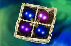Christmas tree baubles. Christmas tree balls arranged in basket on blue and green background Stock Image