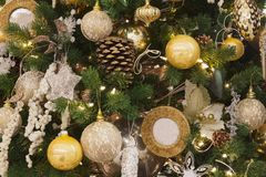 Christmas tree with beautiful baubles and pine cones. Glowing garlands on green spruce. royalty free stock images