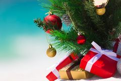 Christmas beach paradise background. Christmas tree on a beautiful white sandy beach paradise in the summer.  Closeup with background blur suitable copyspace Royalty Free Stock Photos
