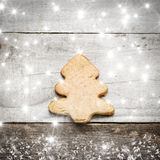 Christmas tree biscuit on grey wooden background. Stars snow and snow flaks image. Christmas tree ornament Stock Image
