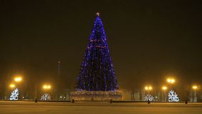 Christmas tree blinking at night. New Year`s mood - Christmas tree blinking with different lights at night during snowfall in the midst of the lanterns around stock footage