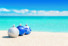 Christmas tree blue and silver balls decorations on beach sand. Christmas tree balls decorations on the sand of tropical ocean beach - happy New Year and Merry royalty free stock image