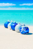 Christmas tree blue and silver balls decorations on beach sand Stock Photos