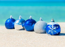 Christmas tree blue and silver balls decorations on sandy beach Royalty Free Stock Image