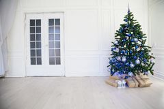 Christmas tree with blue in a white room with toys for Christmas. 1 Royalty Free Stock Images