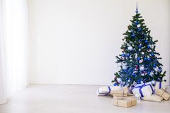 Christmas tree with blue in a white room with toys for Christmas. 1 Royalty Free Stock Photos