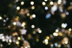 Christmas tree bokeh light in green yellow golden color, holiday abstract background, blur defocused with grain hipster color. Stock Image