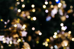 Christmas tree bokeh light in green yellow golden color, holiday abstract background, blur defocused with grain hipster color. royalty free stock photography