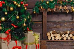 Christmas tree, boxes of gifts. Wooden brown wall with decorative logs coniferous branches royalty free stock photo