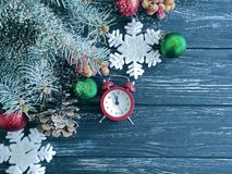 Christmas tree branch alarm clock december on wooden snow background. Christmas tree branch alarm clock wooden snow background december royalty free stock images