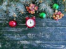 Christmas tree branch alarm decoration retro festive clock december on wooden snow background. Christmas tree branch alarm clock wooden snow background december royalty free stock photo