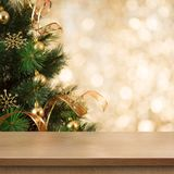 Christmas tree branch behind empty wood table or shelf. Christmas tree branch with gold backgound behind empty table or shelf royalty free stock image