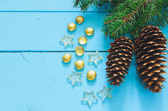Christmas tree branch with cone. On blue wooden background, marbles, stars Royalty Free Stock Images