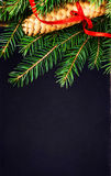 Christmas Tree Branch with cone and red ribbon on Black board wi. Th copy space for greeting text. Christmas card with decoration Stock Photos