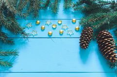 Christmas tree branch with cone. On a wooden background, marbles, stars Stock Photography