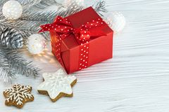 Christmas tree branch decorated with garland, red gift box and g Stock Photo
