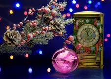 Christmas tree branch with decoration ball. Clock in fairy background. Royalty Free Stock Images